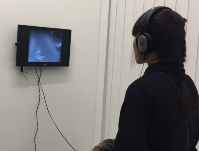 Visitor watches a video with headphones