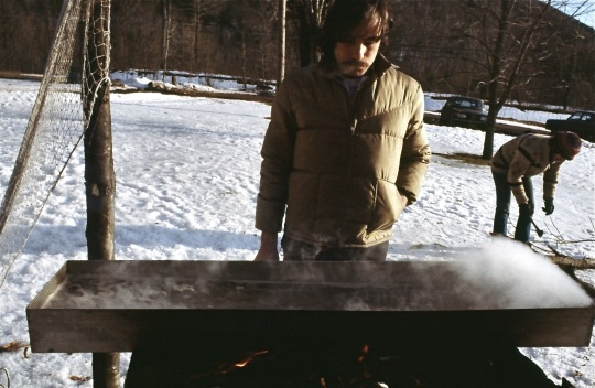 Chuck stands at a steaming pan of maple sap